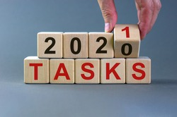 Business concept of planning 2021. Male hand flips wooden cube and change the inscription 'Tasks 2020' to 'Tasks 2021'. Beautiful grey background, copy space.