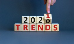 Business concept of planning 2021. Male hand flips wooden cube and change the inscription 'TRENDS 2020' to 'TRENDS 2021'. Beautiful grey background, copy space.