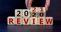 Business concept of planning 2021. Male hand flips wooden cubes and changes the inscription 'Review 2020' to 'Review 2021'. Beautiful dark wooden background, copy space.