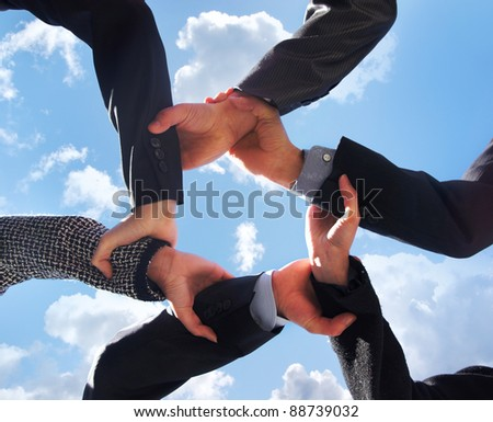 Business concept of some hands over sky background
