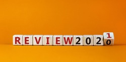 Business concept of starting 2021. Fliped a wooden cube and changes the inscription 'Review 2020' to 'Review 2021'. Beautiful orange background, copy space.