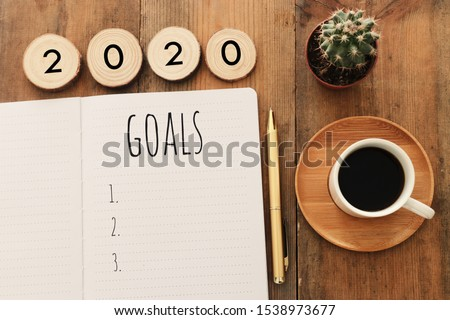 Business concept of top view 2020 goals list with notebook, cup of coffee over wooden desk