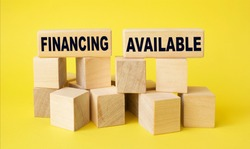 Business concept on wooden cubes. Text Financing is available. Yellow background