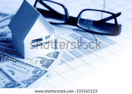 Business concept. Paper house near spectacles on one dollar bank notes on paper with chart