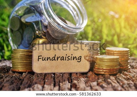 Business Concept - Paper tag written with FUNDRAISING inscription. Coins stack, jar and nature background.  #581362633