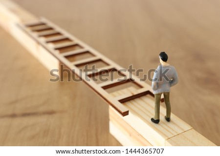 business concept picture of challenge. A man stands on the edge of a high wall and passes the gap by placing a ladder. Problem solving and decisionmaking.