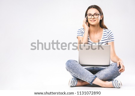 Business concept. Portrait of woman in casual sitting on floor in lotus pose and holding laptop isolated over white background. Using phone.  #1131072890