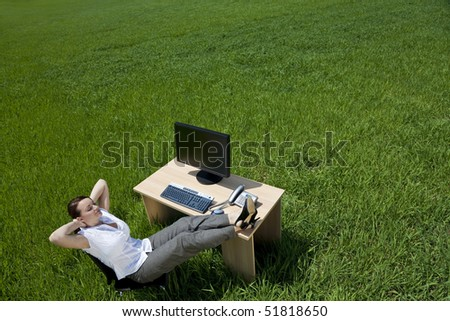 Business concept shot of a beautiful young woman relaxing at a desk in a green field. Shot on location.