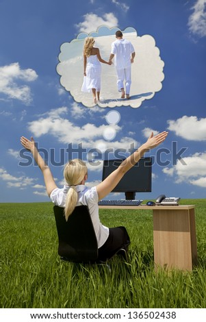 Business concept shot of a beautiful young woman sitting at a desk using a computer in a green field raising her arms into the sky daydreaming of being on tropical beach with her husband or boyfriend
