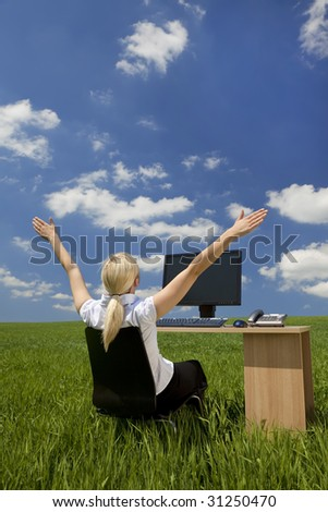 Business concept shot of a beautiful young woman sitting at a desk using a computer in a green field raising her arms into the sky. Shot on location with copy space. #31250470