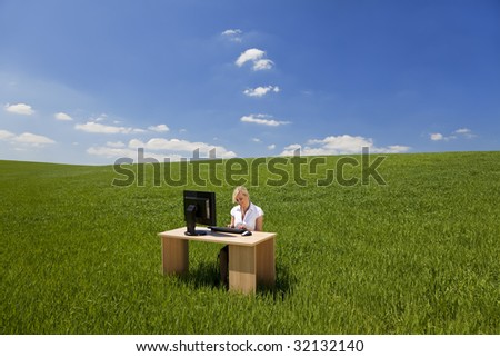 Business concept shot of a beautiful young woman sitting at a desk using a computer in a green field raising her arms into a bright blue sky with fluffy white clouds.