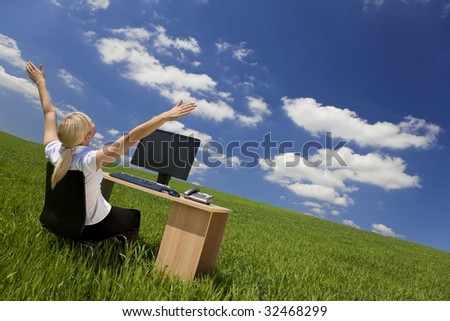 Business concept shot of a beautiful young woman sitting at a desk using a computer in a green field raising her arms into a bright blue sky. Shot on location with copy space. #32468299