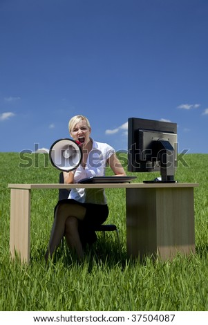 Business concept shot of a beautiful young woman sitting at a desk using a megaphone in a green field with a bright blue sky. Shot on location.