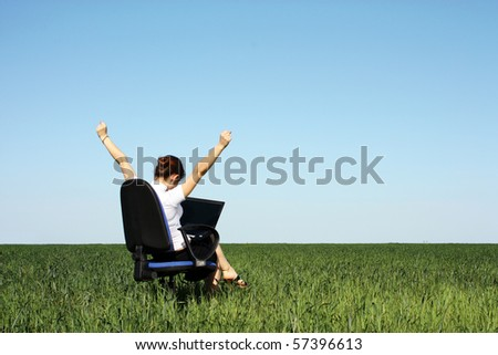 Business concept shot of a beautiful young woman sitting on chair using a computer in a green field