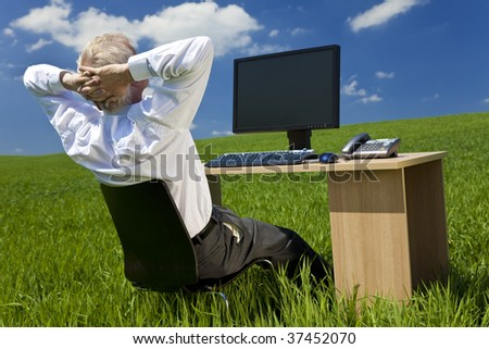 Business concept shot showing an older male executive relaxing at his desk with a computer in a green field with a blue sky complete with fluffy white clouds. Shot on location not in a studio.