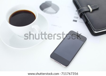 Business concept shot with coffee, phone and chart on table