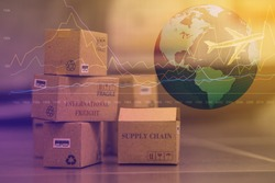 business concept: Small cardboard boxes with a plane flies above world map. Concept of  transportation, international freight, global shipping, goods or services remotely.  overseas trade, regional