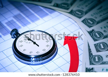 Business concept. Stopwatch on paper background with chart and money