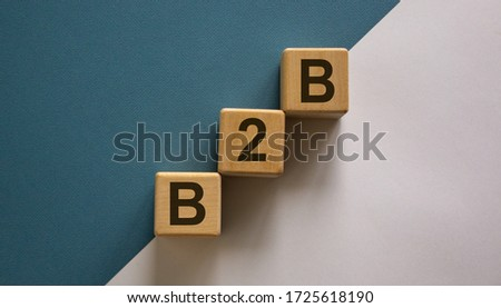 Business concept success process. Wood block with letteres b2b stacking as step stair on paper blue and white background, copy space. Stockfoto ©
