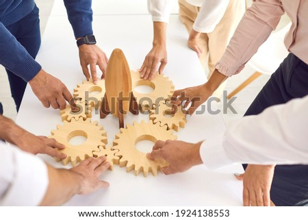 Business concept. Team of cropped company employees join gearwheels around toy rocket as metaphor for unity, teamwork, choosing new effective strategy and launching new project