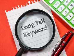 Business concept.Text Long Tail Keyword writing on notepaper with magnifying glass,calculator and pen on a red background.