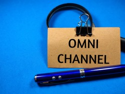 Business concept.Text OMNI CHANNEL writing on brown card with pen and magnifying glass on a blue background.