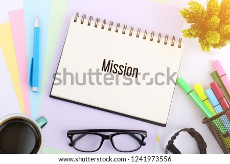 Business concept. top view notebook with pen, glasses and coffee cup writing Mission #1241973556