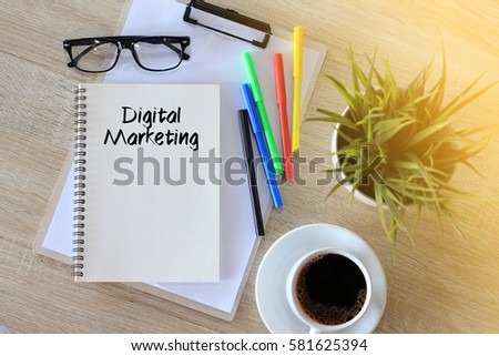 Business concept - Top view notebook writing Digital Marketing