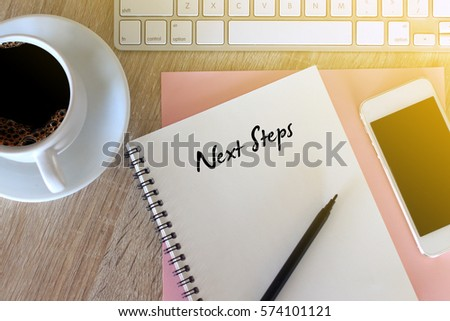 Business concept - Top view notebook writing Next Step
