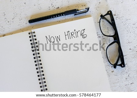 Business concept - Top view notebook writing Now Hiring