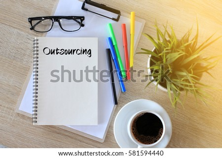 Business concept - Top view notebook writing Outsourcing