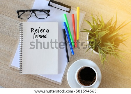 Business concept - Top view notebook writing Refer a Friend