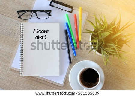 Business concept - Top view notebook writing Scam Alert