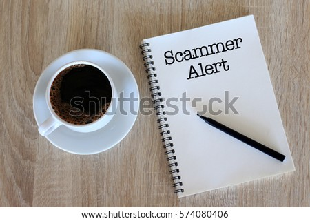Business concept - Top view notebook writing Scammer Alert