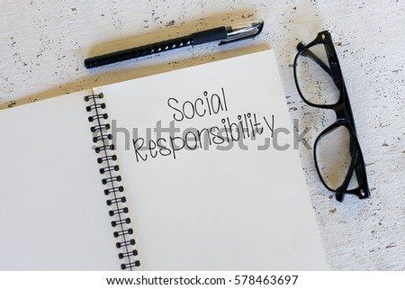 Business concept - Top view notebook writing Social Responsibility