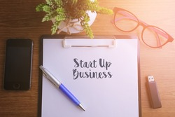 Business concept - Top view notebook writing Start Up Business