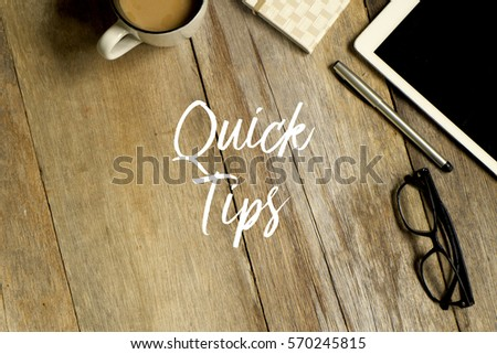 Business concept. Top view of tablet, glasses. notebook pen and a cup of coffee with QUICK TIPS written on wooden background.