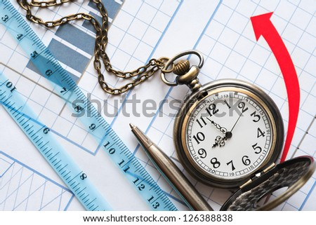 Business concept. Watch and ruler on paper background with red chart