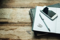 Business concept with paper agenda pen and smartphone on the wood table