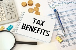 Business concept - workspace office desk and notebook writing TAX BENEFITS