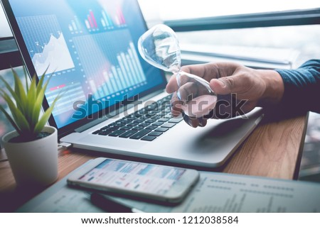 Business concepts with businessman holding hourglass with graph chart on computer laptop.For investment analysis,Waiting to sucess ideas