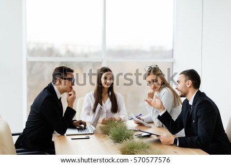 Business conference. Business meeting. Business people in formal wear discussing something while sitting together at the table