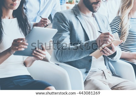 Business conference. Close-up of young people sitting on conference together and making notes