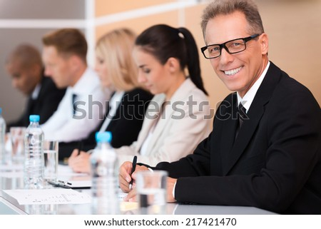 Business conference. Group of business people sitting in a row and writing something in their note pads while confident mature man in formalwear looking at camera and smiling