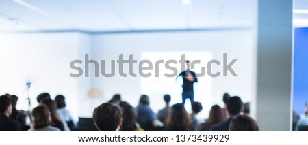 Business Conference Photo. Executive Speaker on Stage. Business Presentation Presenter Speech at Tech Entrepreneur Meeting. Corporate Event Audience. Expert Seminar Lecture Conference Event. Blurred.