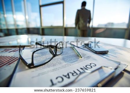 Business contract, pen, eyeglasses, market analysis and cellphone on desk and businessman standing on background