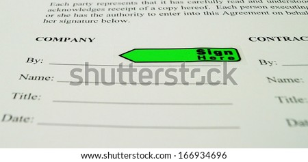 Business Contract Sign the Dotted Line. A sign here flag marks the signature line on a business agreement.