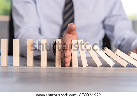 Business control concept by stopping domino effect