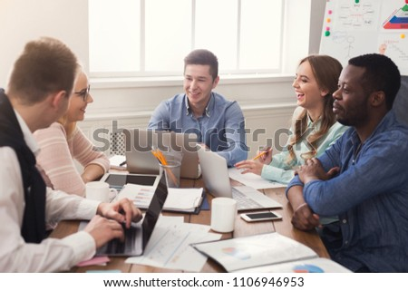 Business corporate meeting of multiethnic team. Young cheerful people brainstorming, discussing new startup project in office, copy space