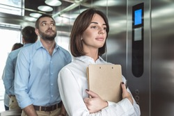 Business couple is rising in elevator